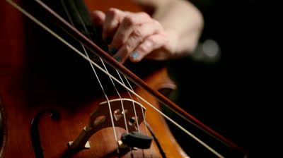 Stock footage detail footage of the hands of a cellist as she demonstrates both bowing and left hand fingering on